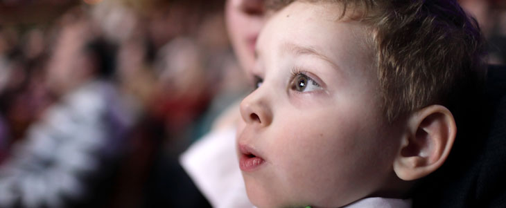 A young child attends a theatre performance with his mother
